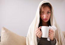 Frau mit Grippe in Pullover eingehüllt mit Tasse und Taschentuch in der Hand