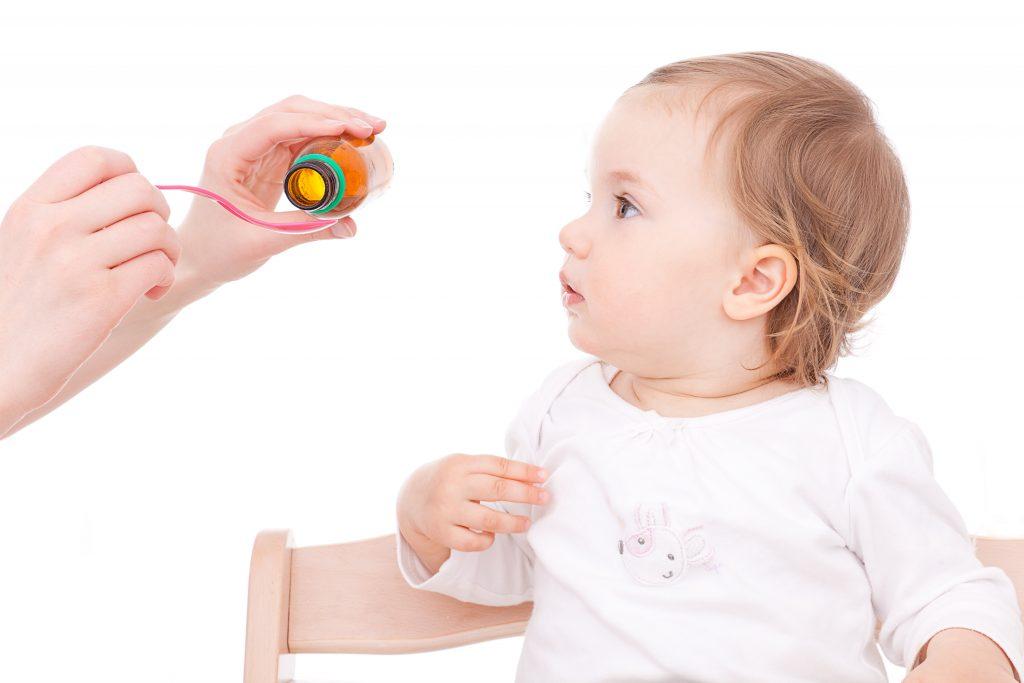 Ein Kleinkind erhält Hustensaft