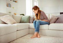 frau auf couch mit bauchschmerzen