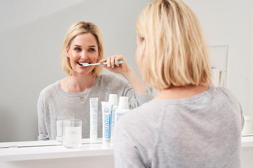 Frau vor einem Spiegel im Badezimmer, putzt sich die Zähne mit Meridol