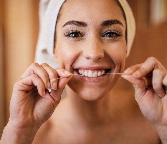 Frau im Badezimmer mit Handtuch auf Kopf benutzt Zahnseide