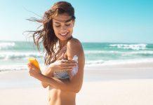 Frau mit Sonnencreme am Strand