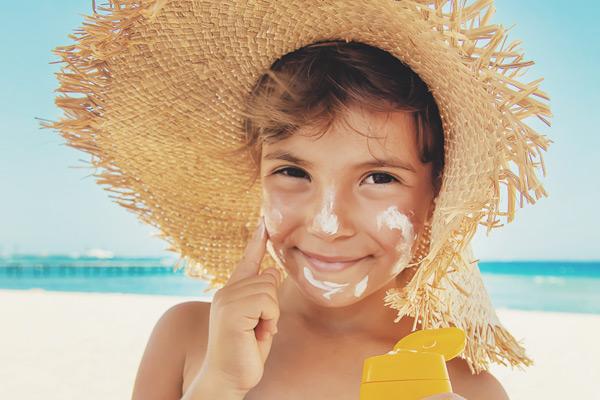 Kleiner Junge mit Strohhut cremt sich ausgiebig mit Sonnencreme ein.